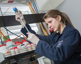 Student testing chemicals in a lab