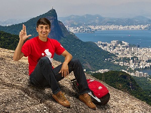 male student sitting on a hill overlooking a city