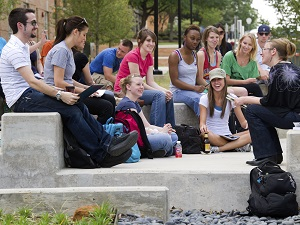 Students sitting on steps in an outdoor lecture